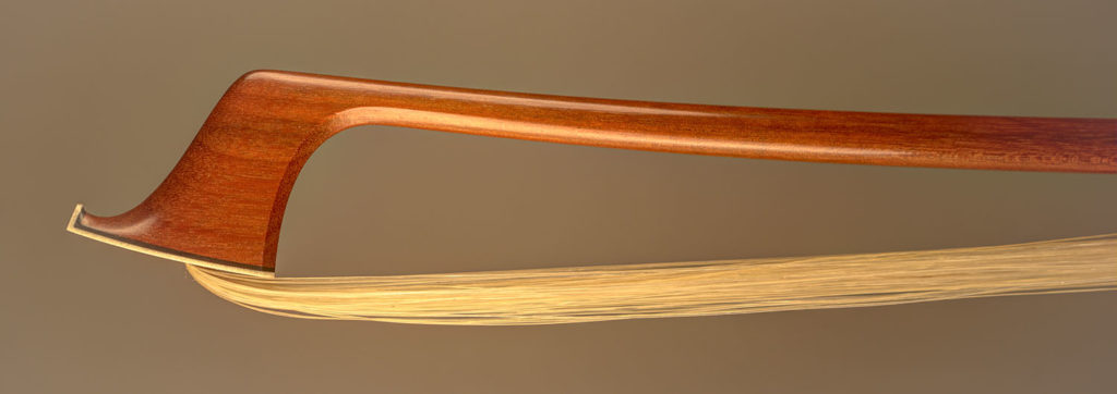 Violin Bow with a round pernambuco stick, silver-mounted ebony frog with double pearl eyes and divided button.