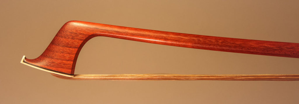 Violin Bow with a round pernambuco stick, silver-mounted ebony frog with plain pearl eyes and divided button.